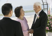 Groom with parents at beach — Stock Photo