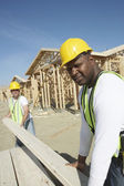 Construction workers stacking timber — Stock Photo