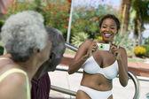 Woman photographing senior couple — Stock Photo