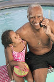 Senior man sitting by pool with granddaughter — Stock Photo