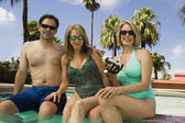 Woman holding camcorder with couple — Stock Photo