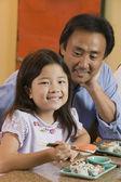 Father Watching Daughter Eat Sushi — 图库照片