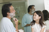 Daughter watching father apply shaving cream — Stock Photo