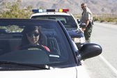 Women in car pulled by police officer — Stock Photo