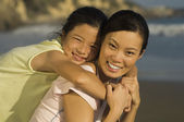 Closeup portrait of young woman piggybacking daughter on beach — Stock Photo