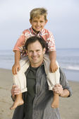 Boy on fathers shoulders at beach — Stock Photo