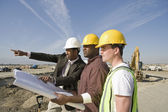 Construction workers with plans — Stock Photo