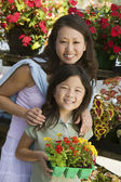 Mother with daughter holding flowers — Stock Photo