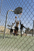 Friends playing basketball on court — Stock Photo