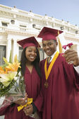 Graduates Holding Flowers and Diploma — Stockfoto