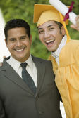 Graduate hoisting diploma — Stock Photo