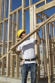 Construction worker holding up plank at site — Stock Photo