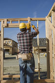 Construction worker hammering nail — Stock Photo