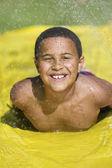 Boy sliding on water slide — Stock Photo