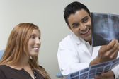 Dentist and patient examining X-rays — Stock Photo