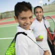 Boy and girl with tennis equipment — Stock Photo