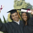 Two graduates hoisting diplomas — Stock Photo #33802283