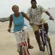 Couple cycling on beach — Stock Photo