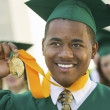 Stock Photo: Graduate Holding Medal