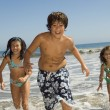 Children running through waves — Stock Photo