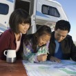 Parents and daughter looking at map — Stock Photo