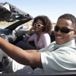 Couple driving convertible on desert road — Stock Photo #33803285