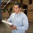 Foto Stock: Mchecking lumber in warehouse