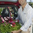 Stock Photo: Man Loading Flowers into Van
