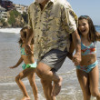 Girls and grandfather running through waves — Stock Photo