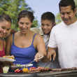 Boy with family at outdoor grill. — Stock Photo