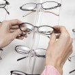 Stock Photo: Hands choosing eyeglasses
