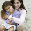 Mother embracing daughter on beach — Stock Photo