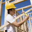 Stock Photo: Worker measuring timber