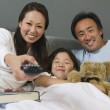 Family Watching TV Together in Bed — Stock Photo