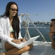 Mwith womusing laptop on sailboat — Stock Photo #33805709