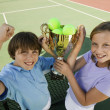 Brother and Sister on tennis court — Stock Photo