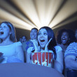 People watching horror movie in the theatre — Stockfoto