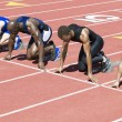 Stock Photo: Male athletics waiting at starting blocks