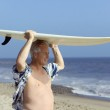 Male surfer carrying surfboard — Stock Photo #33808253
