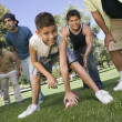 Boy playing football with group of men. — Stock Photo #33808271