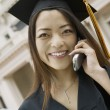 Graduate with Gift Using Cell Phone — Stock Photo