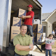 Stock Photo: Family and worker unloading boxes