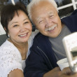 Asian Couple using mobile phone — Stock Photo