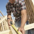 Stock Photo: Construction worker measuring timber