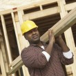 Foto Stock: Construction worker carrying lumber