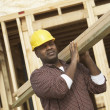 Stock Photo: Construction worker carrying lumber