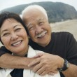 Mature couple embracing on beach — Stock Photo #33809179