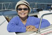 Woman wearing sunglasses on sailboat — Stock Photo