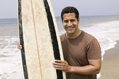 Man holding surfboard on beach — Stok fotoğraf