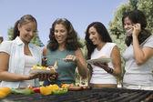Women around outdoor grill. — Stock Photo